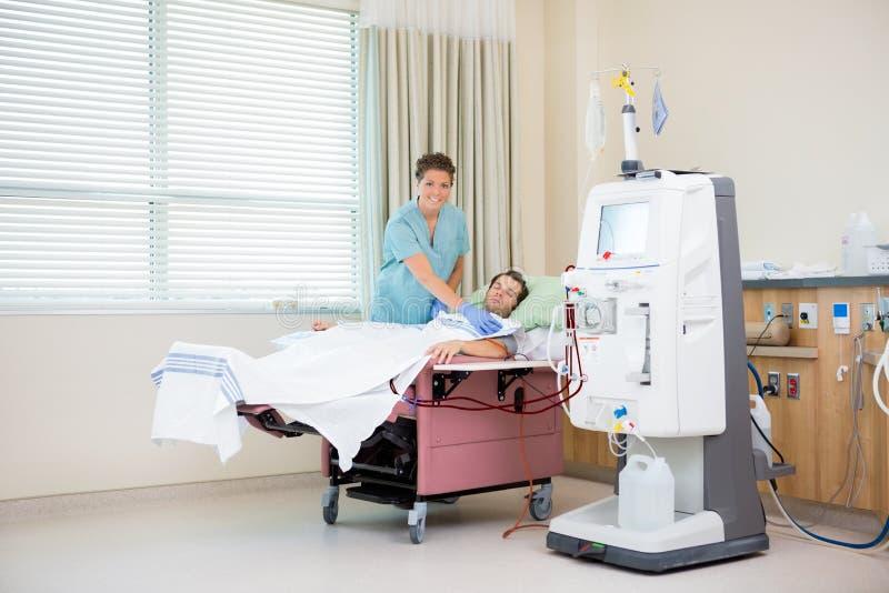 Retrato de la enfermera By Patient Receiving renal imagen de archivo libre de regalías