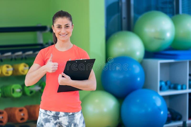 Retrato de la escritura femenina sonriente del instructor de la aptitud en tablero mientras que se coloca en gimnasio foto de archivo