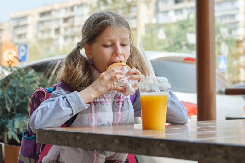 Retrato de la estudiante con la mochila, comiendo la hamburguesa con el zumo de naranja, fondo del café al aire libre de los alim fotografía de archivo libre de regalías