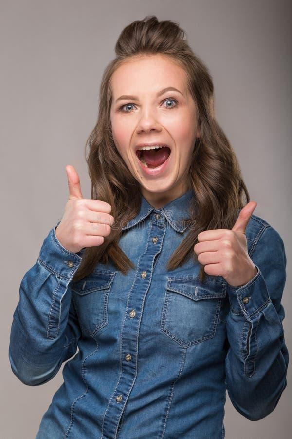 Retrato de la estudiante enérgica de la diversión en un fondo gris en a imagenes de archivo