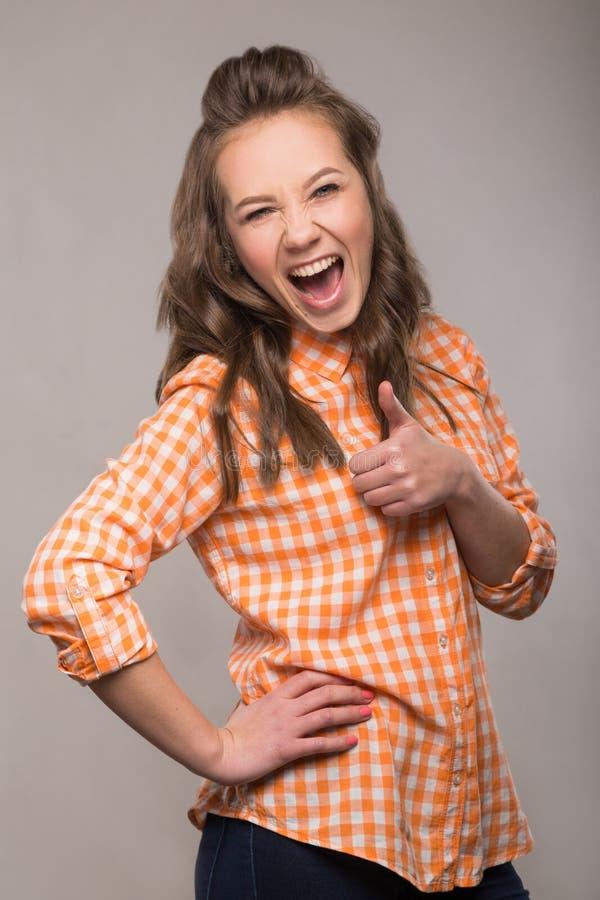 Retrato de la estudiante enérgica de la diversión en un fondo gris en a foto de archivo libre de regalías