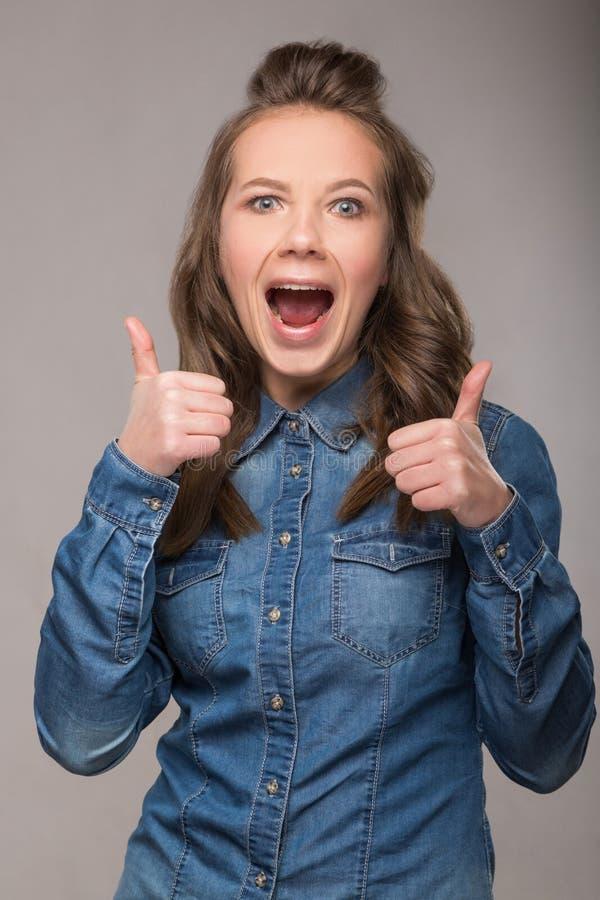 Retrato de la estudiante enérgica de la diversión en un fondo gris en a fotos de archivo libres de regalías