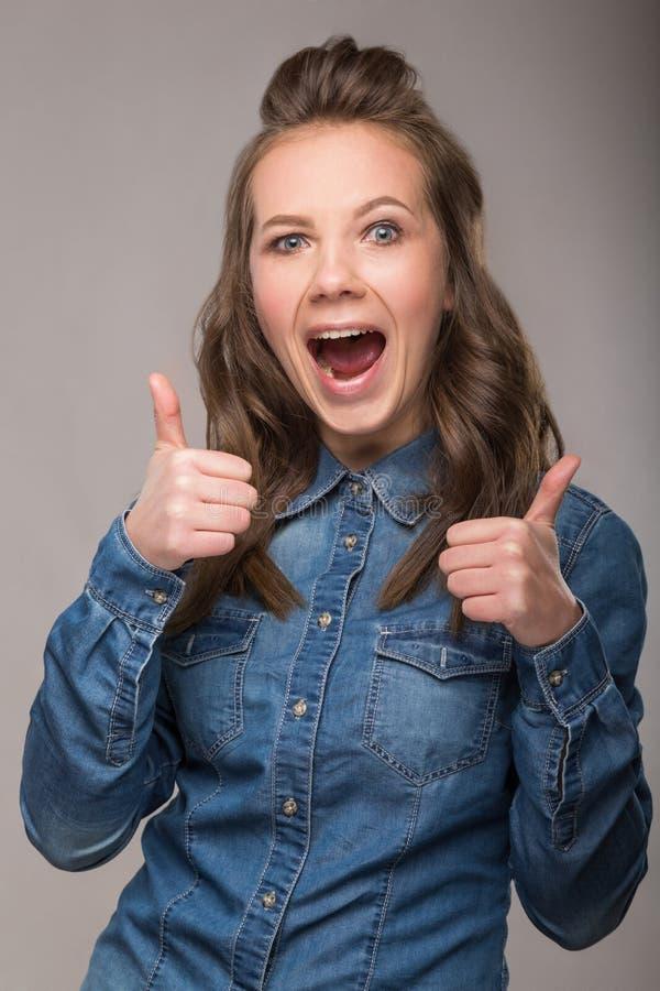 Retrato de la estudiante enérgica de la diversión en un fondo gris en a imagen de archivo libre de regalías