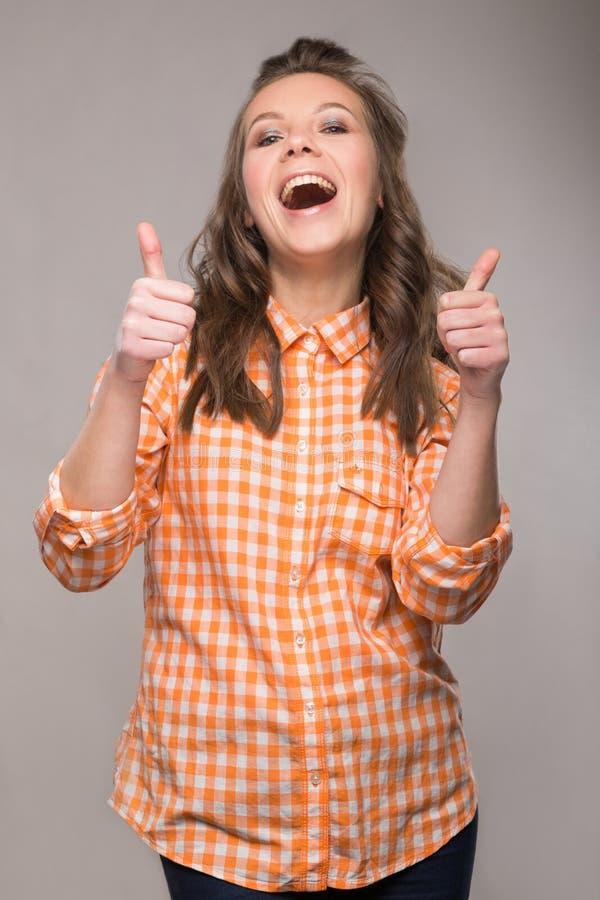 Retrato de la estudiante enérgica de la diversión en un fondo gris en a fotos de archivo