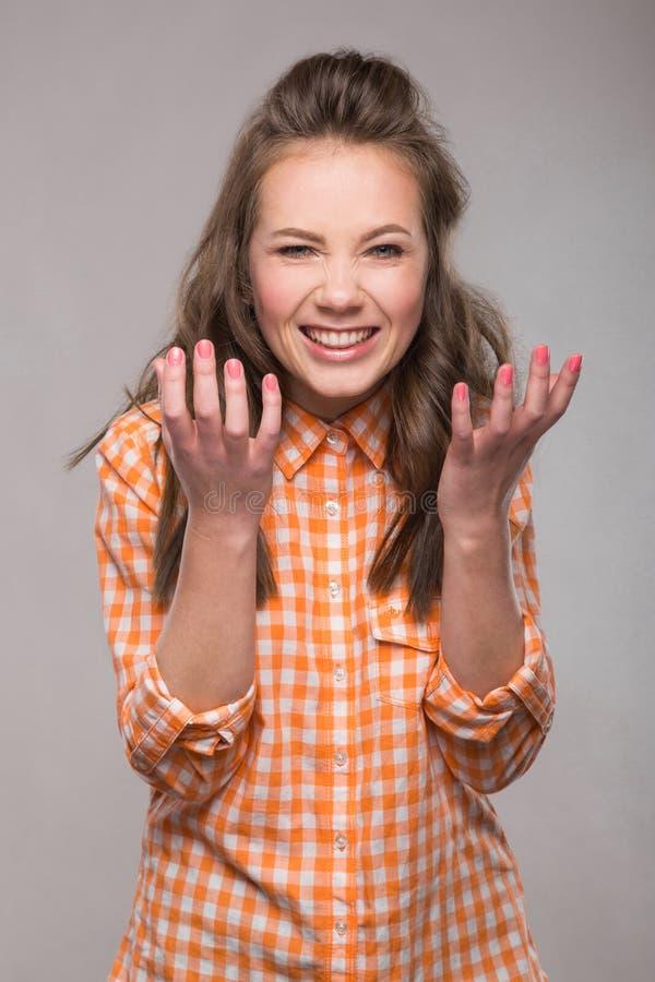 Retrato de la estudiante enérgica de la diversión en un fondo gris en a imágenes de archivo libres de regalías