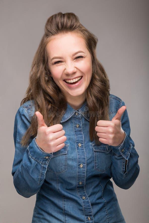 Retrato de la estudiante enérgica de la diversión en un fondo gris en a imagen de archivo