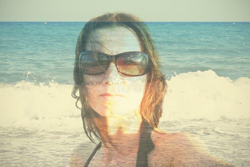 Retrato de la exposición doble de una mujer joven en fondo de la playa del verano foto de archivo