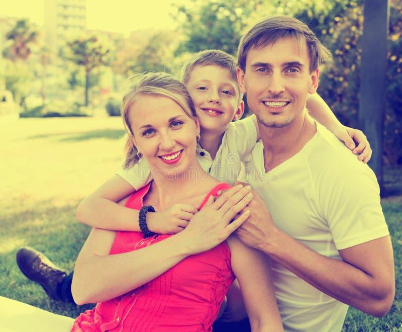 Retrato de la familia alegre con el muchacho en de escuela de la edad huggi feliz fotografía de archivo