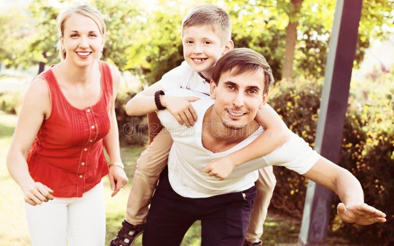 Retrato de la familia alegre con el muchacho que se sienta en la parte posterior del ` s del padre foto de archivo