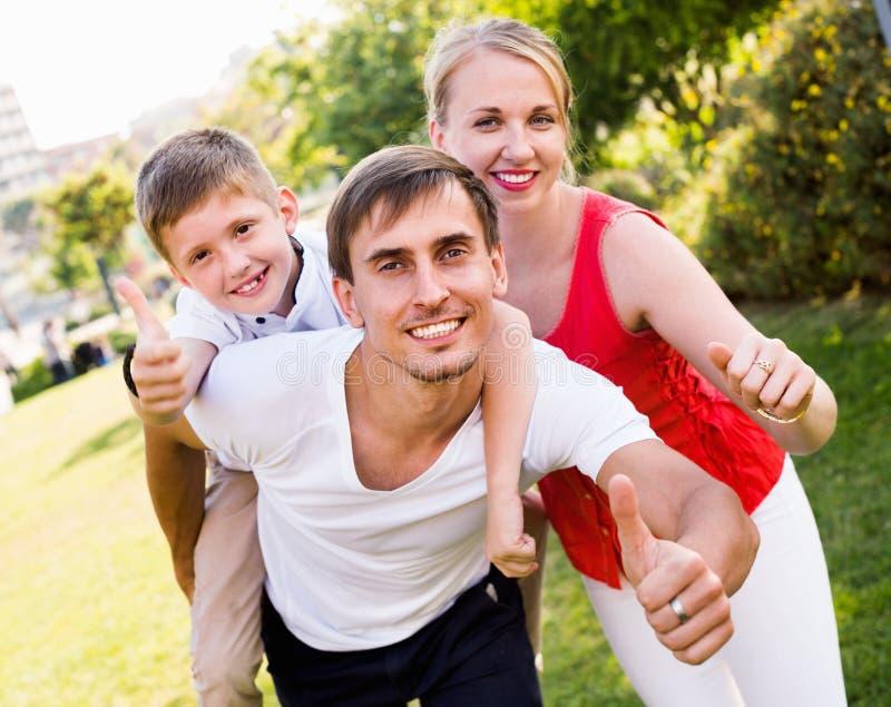 Retrato de la familia alegre con el muchacho que se sienta en la parte posterior del ` s del padre imagen de archivo libre de regalías