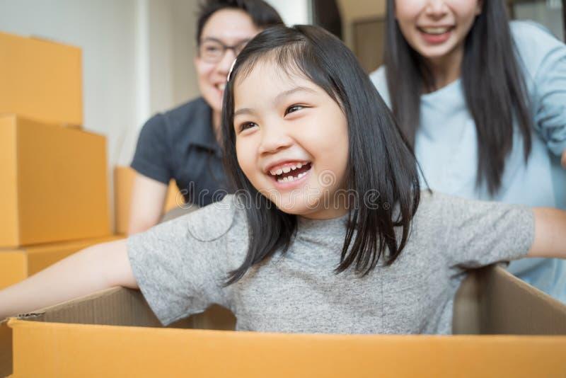 Retrato de la familia asiática feliz que se mueve a la nueva casa con las cajas de cartón y que juega la caja de cartón imagen de archivo