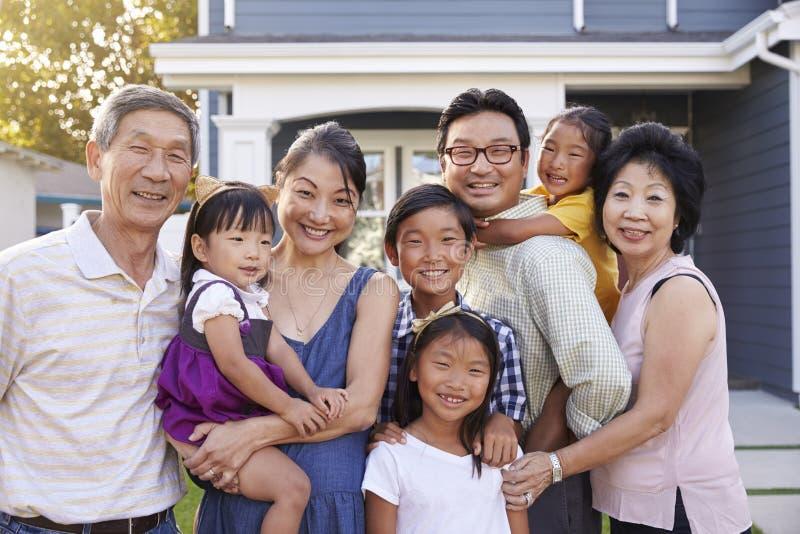 Retrato de la familia con los abuelos que colocan la casa exterior fotos de archivo libres de regalías