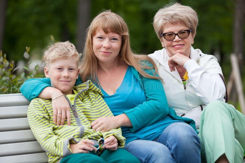 Retrato de la familia con la madre, el hijo joven y la abuela mayor sentándose junto en banco en el parque del verano fotos de archivo libres de regalías