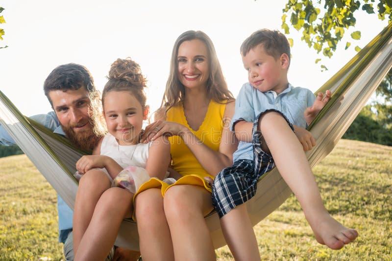 Retrato de la familia con la madre hermosa de dos niños al lado de su marido imagenes de archivo