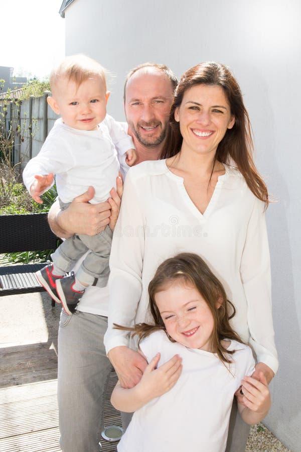 Retrato de la familia de cuatro Los padres felices son al aire libre con dos niños alegres - pequeño muchacho rubio, muchacha mor foto de archivo