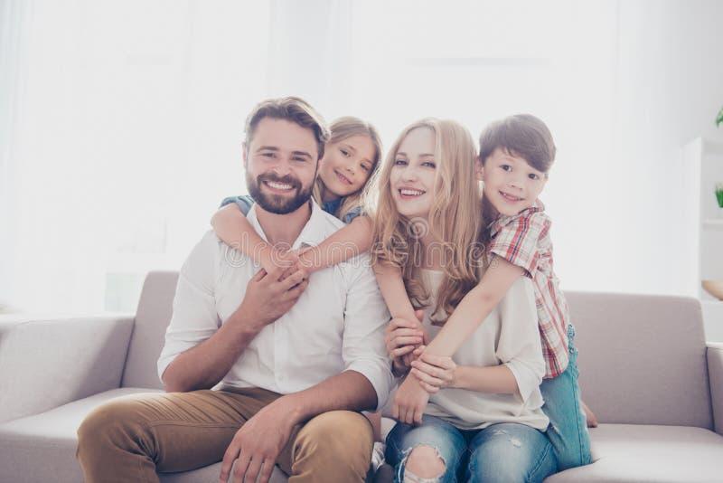 Retrato de la familia de cuatro Los padres felices son el llevar a cuestas su foto de archivo
