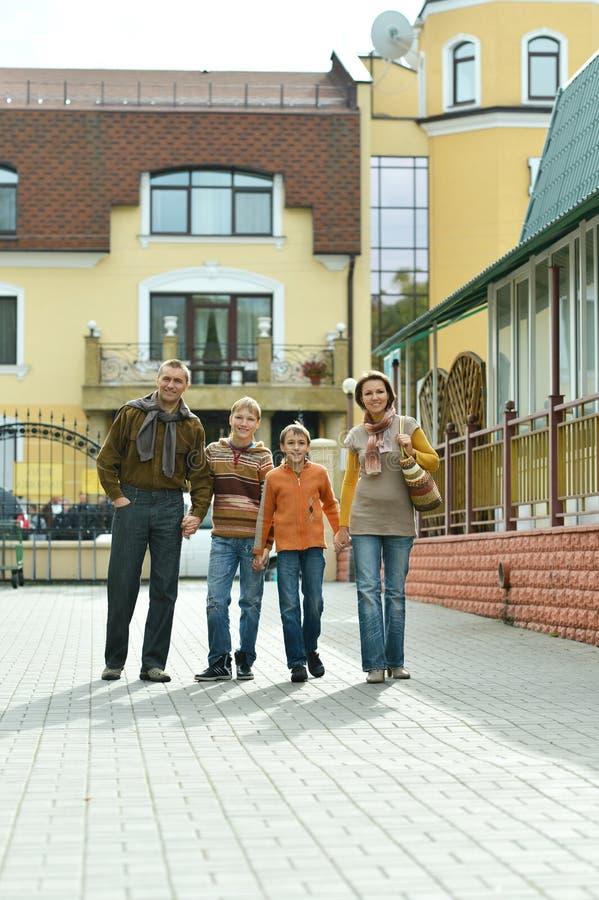 Retrato de la familia de cuatro miembros feliz que camina en la ciudad fotografía de archivo