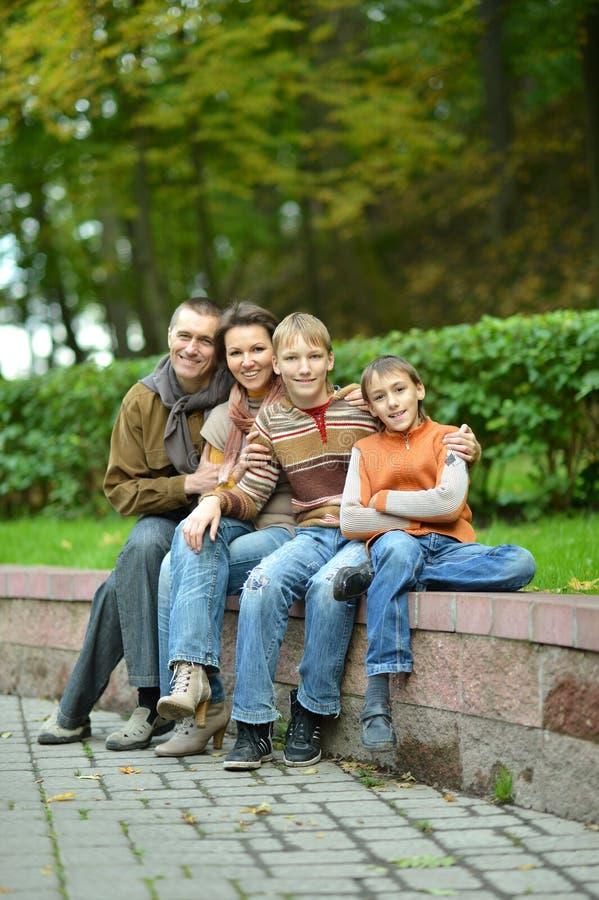 Retrato de la familia de cuatro miembros que se sienta en parque fotos de archivo