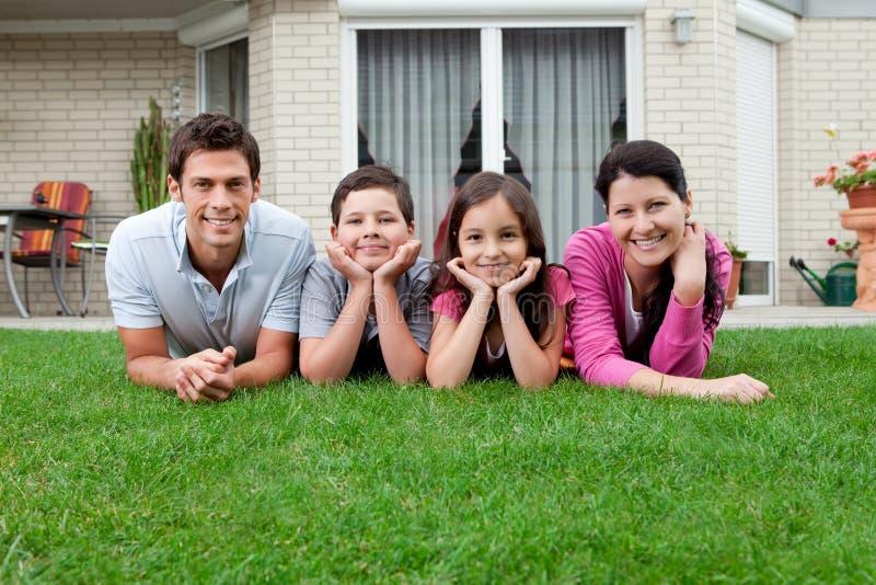 Retrato de la familia de cuatro miembros que miente en patio trasero fotos de archivo libres de regalías