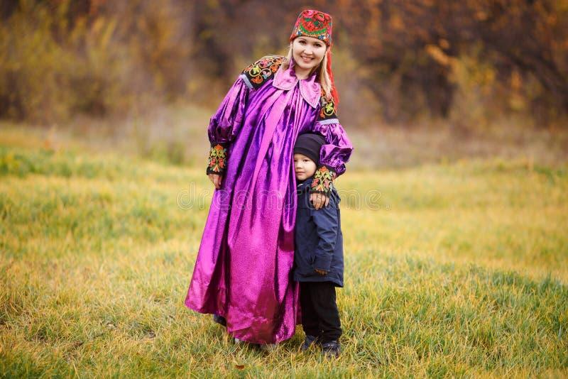 Retrato de la familia de la madre con su hijo al aire libre en traje nacional tradicional Colores del otoño, ornamentos asiáticos imágenes de archivo libres de regalías