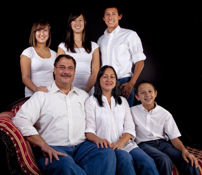 Retrato de la familia encendido asentado con el fondo negro imágenes de archivo libres de regalías