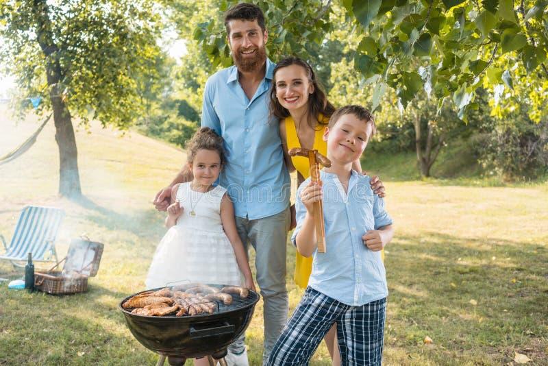 Retrato de la familia feliz con dos niños que se colocan al aire libre imagen de archivo libre de regalías