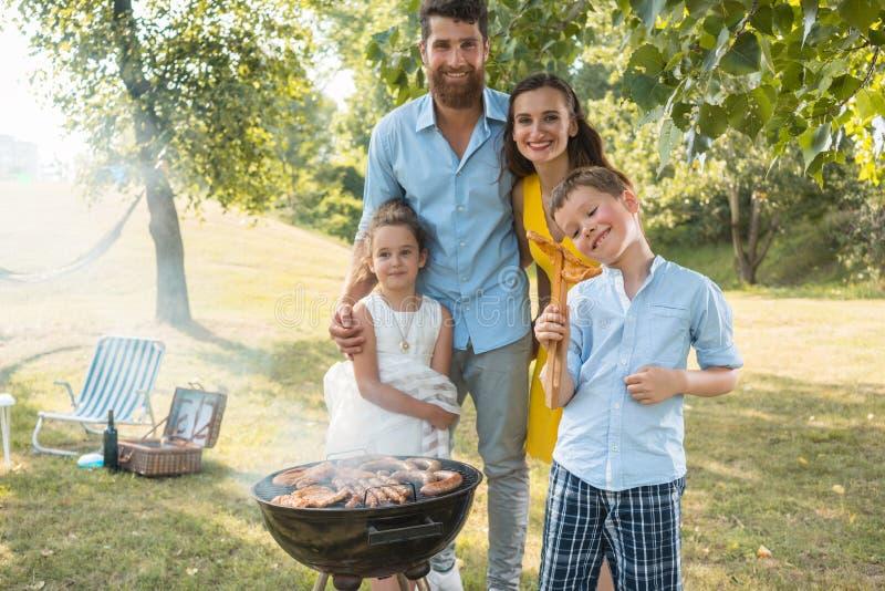Retrato de la familia feliz con dos niños que se colocan al aire libre cerca de una barbacoa fotos de archivo libres de regalías