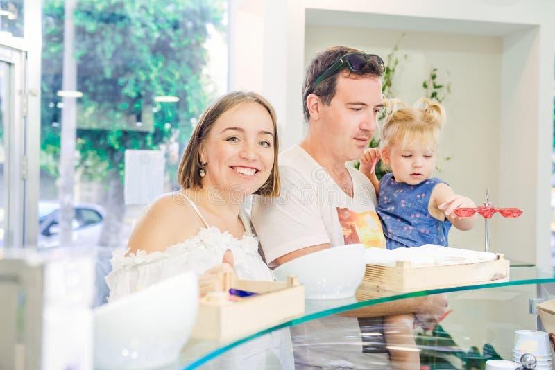 Retrato de la familia feliz con la pequeña niña pequeña linda que elige el helado en el colmado, confitería Comportamiento malsan imagen de archivo libre de regalías