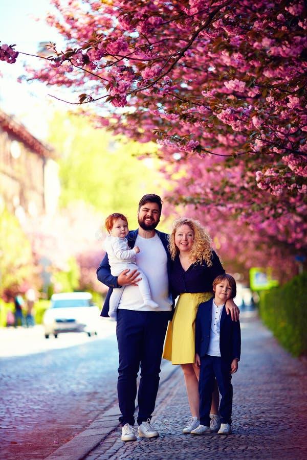 Retrato de la familia feliz en el paseo a lo largo de la calle floreciente de la primavera fotografía de archivo libre de regalías