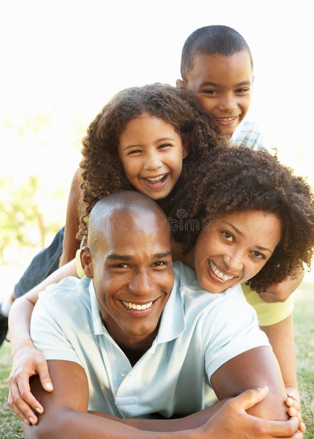 Retrato de la familia feliz llenado para arriba en parque foto de archivo libre de regalías