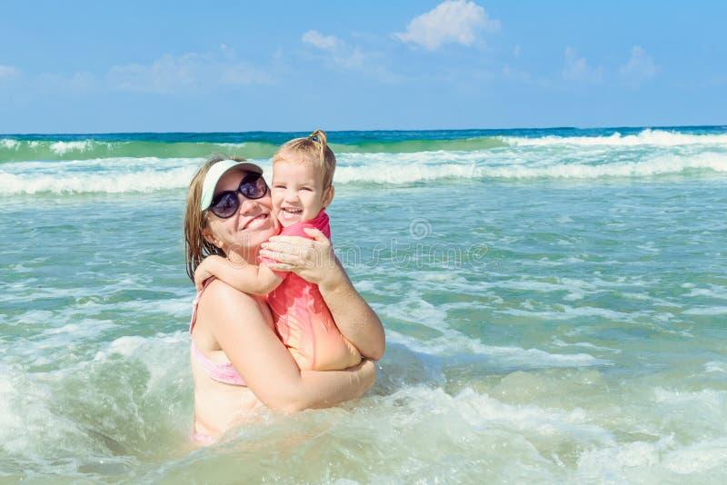 Retrato de la familia feliz - madre con la hija del niño en el traje de natación de protección del sol que se divierte la diversi fotos de archivo