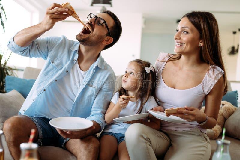 Retrato de la familia feliz que comparte la pizza en casa foto de archivo libre de regalías