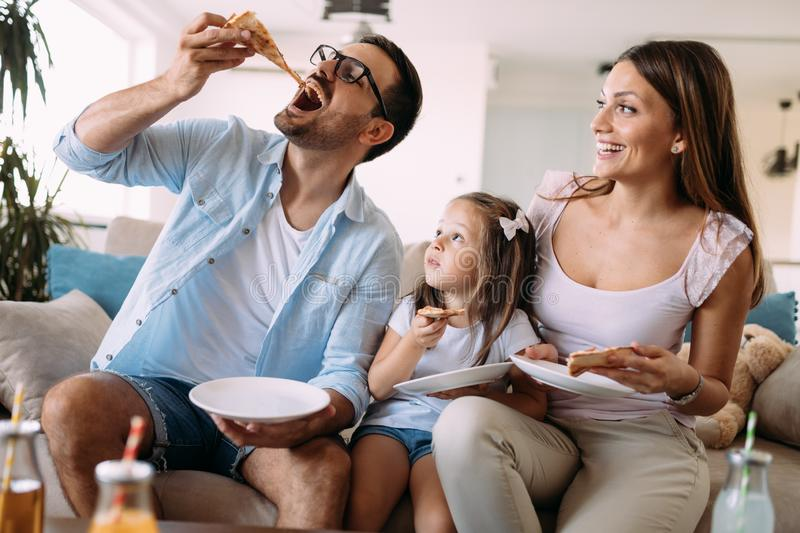 Retrato de la familia feliz que comparte la pizza en casa fotografía de archivo libre de regalías