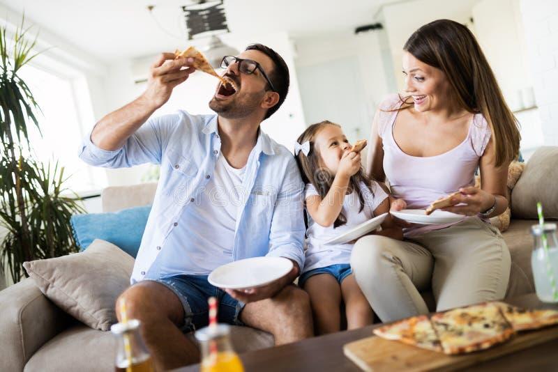Retrato de la familia feliz que comparte la pizza en casa fotos de archivo libres de regalías