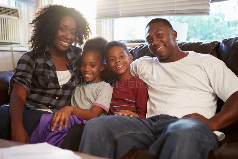 Retrato de la familia feliz que se sienta en el sofá junto imagen de archivo libre de regalías