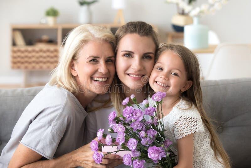 Retrato de la familia feliz de tres mujeres de las generaciones que celebra el bir fotos de archivo