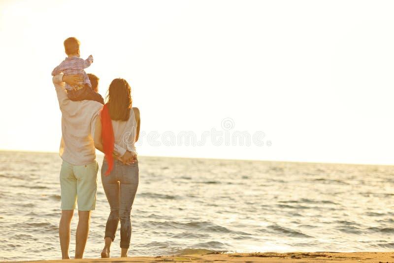 Retrato de la familia feliz y del bebé que disfrutan de puesta del sol en el ocio del verano foto de archivo libre de regalías