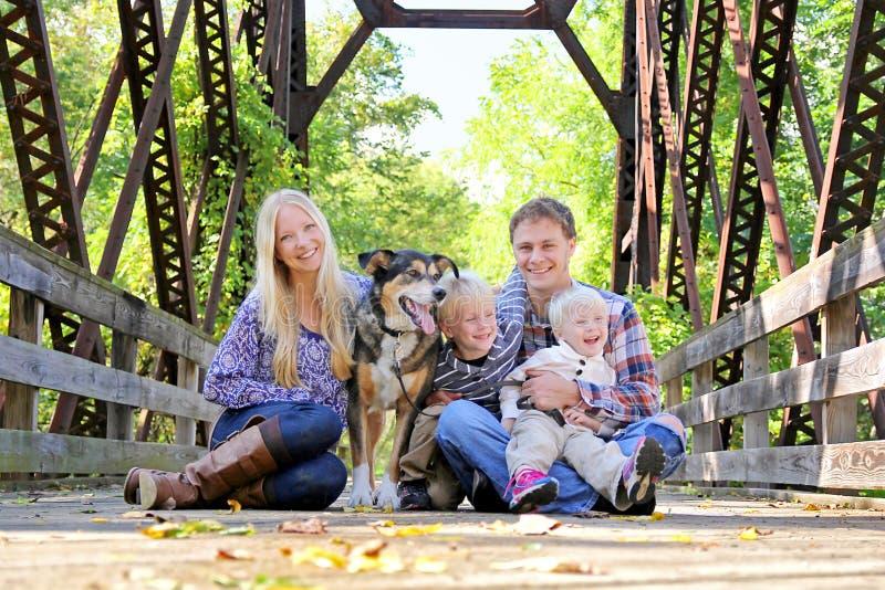Download Retrato De La Familia Feliz Y Del Perro Que Se Sientan En El Puente En Autumn Woo Foto de archivo - Imagen de mezcla, cuatro: 44852152