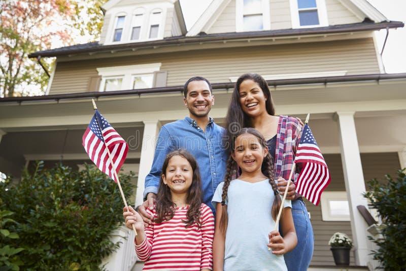 Retrato de la familia fuera de la casa que sostiene banderas americanas fotos de archivo libres de regalías