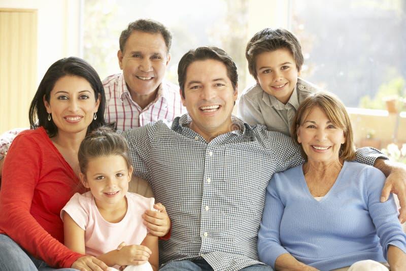Retrato de la familia hispánica extendida que se relaja en casa imagen de archivo