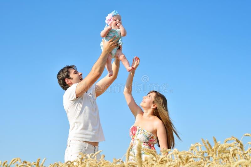 Retrato de la familia Imagen del padre cariñoso feliz, de la madre y de su bebé al aire libre Papá, mamá y niño contra el cielo a foto de archivo libre de regalías