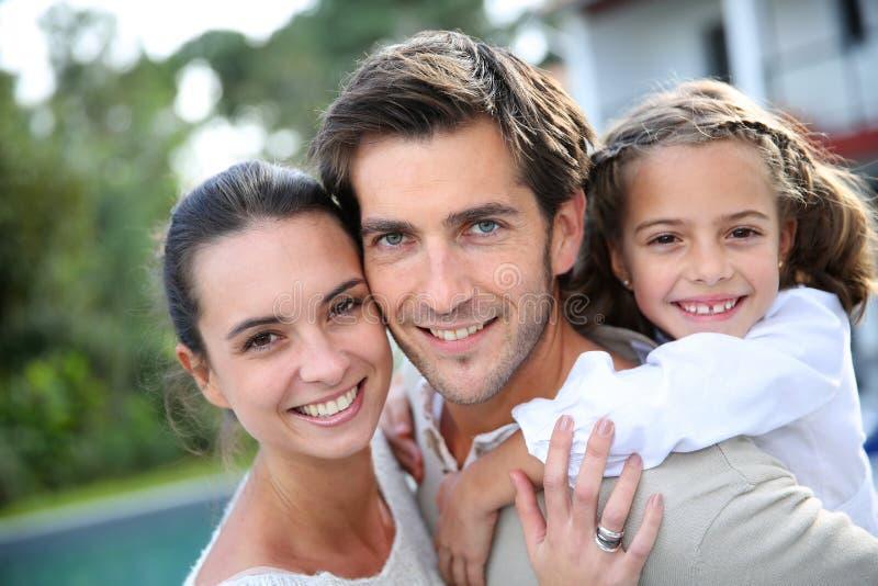 Retrato de la familia joven delante de su hogar fotos de archivo