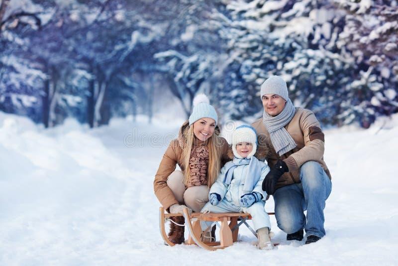 Retrato de la familia joven en un parque del invierno imagenes de archivo