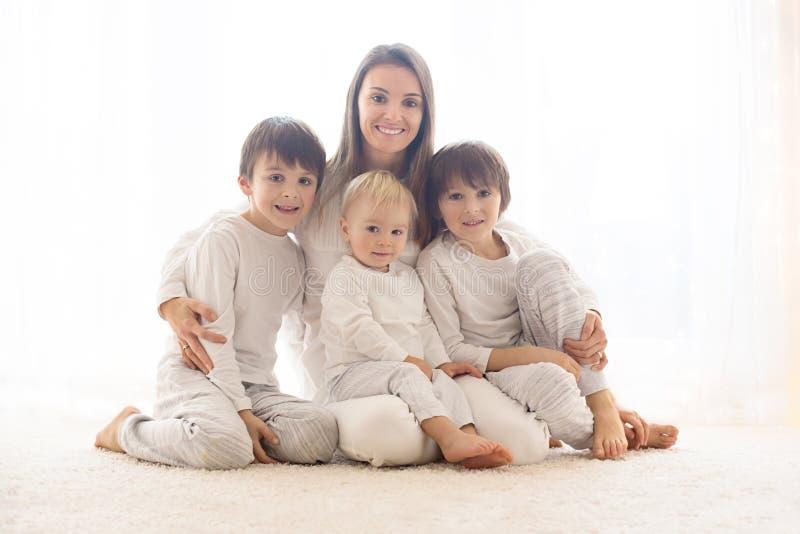 Retrato de la familia de la madre y de sus tres muchachos, aislado en blanco imagenes de archivo