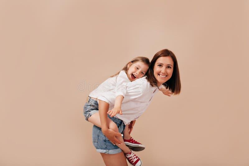 Retrato de la familia de la mujer joven con la hija hermosa, montando en ella detrás sobre fondo aislado imagenes de archivo