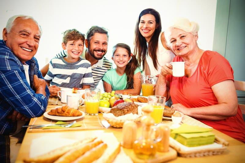 Retrato de la familia multi feliz de la generación que se sienta en la mesa de desayuno foto de archivo