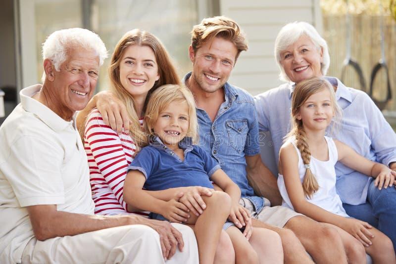 Retrato de la familia multi de la generación que se relaja en cubierta en casa imágenes de archivo libres de regalías