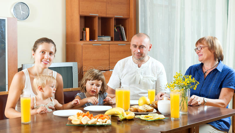 Retrato de la familia multigeneración feliz que come friuts con jui fotografía de archivo