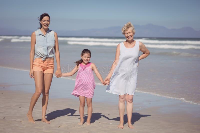 Retrato de la familia multigeneración feliz que lleva a cabo las manos en la playa foto de archivo