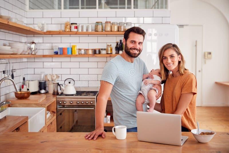 Retrato de la familia ocupada en cocina en el desayuno con el hijo de Caring For Baby del padre imagenes de archivo